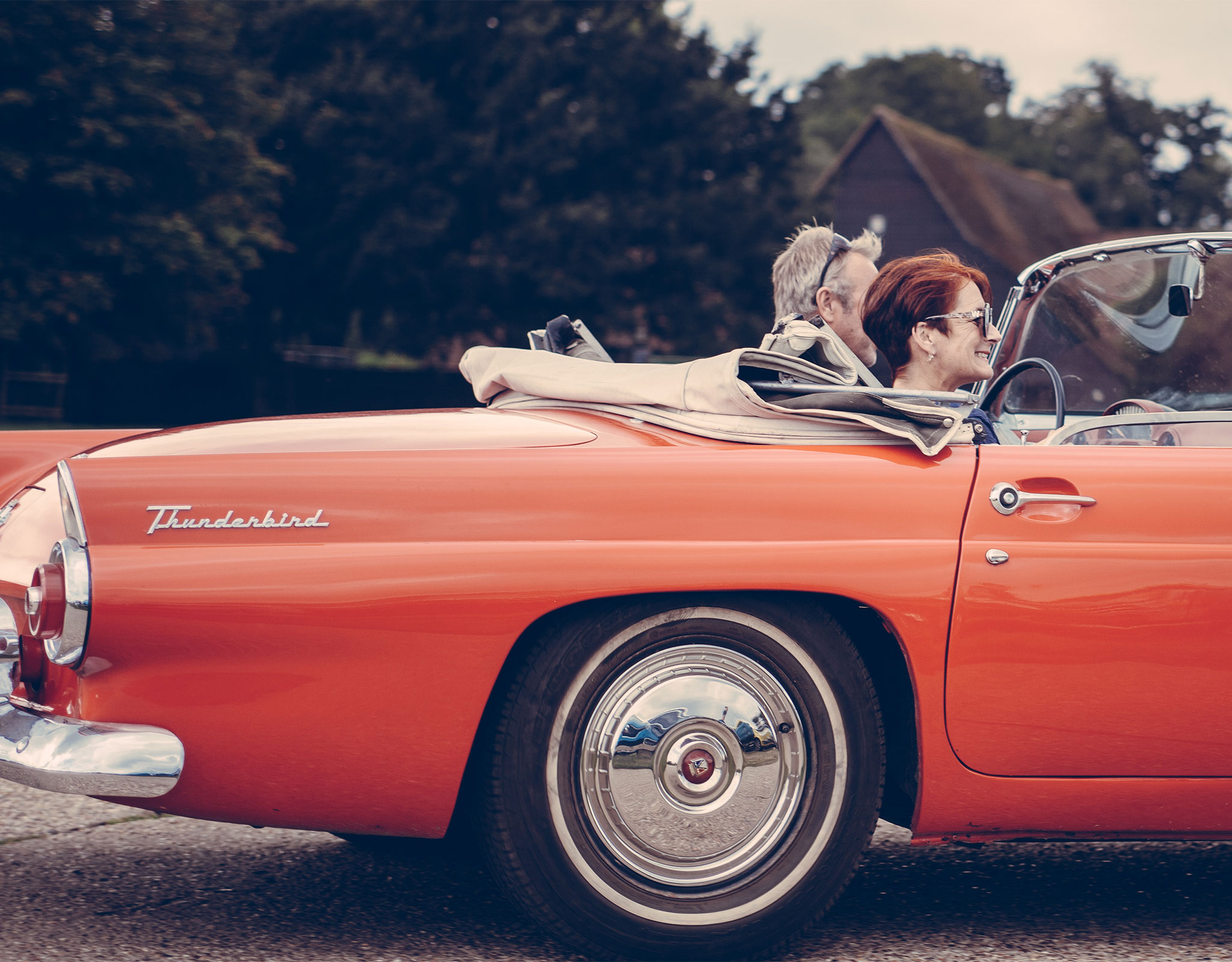 Senior couple riding in a classic red Thunderbird