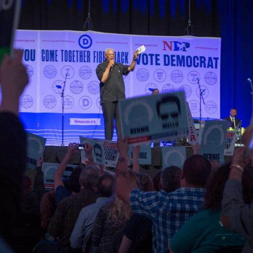 People holding up sign at a political rally