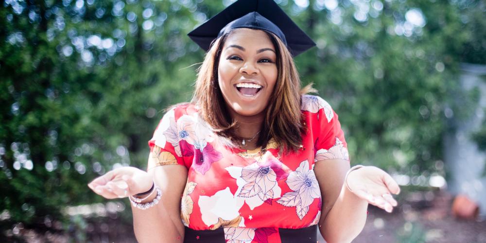 Girl wearing graduation cap in a flower dress smiling.