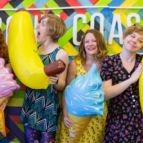 Women holding inflatable bananas and laughing