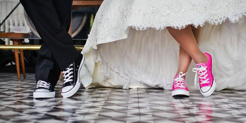 Groom and Bride's legs showing the are wearing Converse All Stars