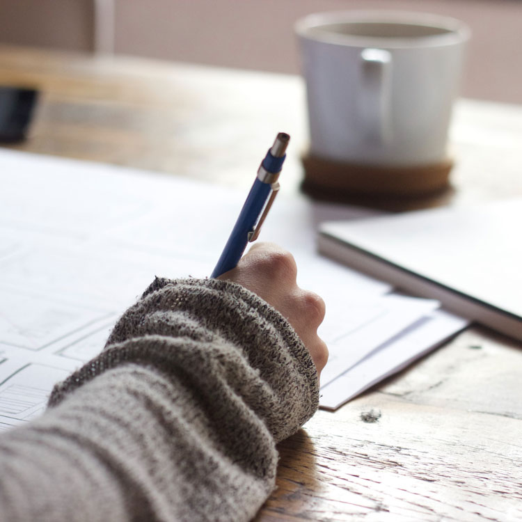 Closeup of person writing check with a cup of coffee nearby.