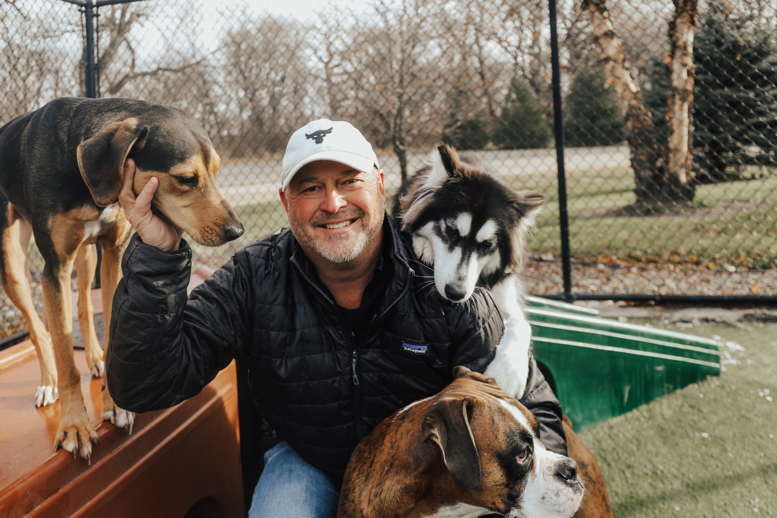 Man smiling with three dogs at his side